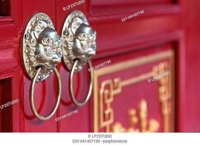 Golden chinese door knockers on a red door, China
