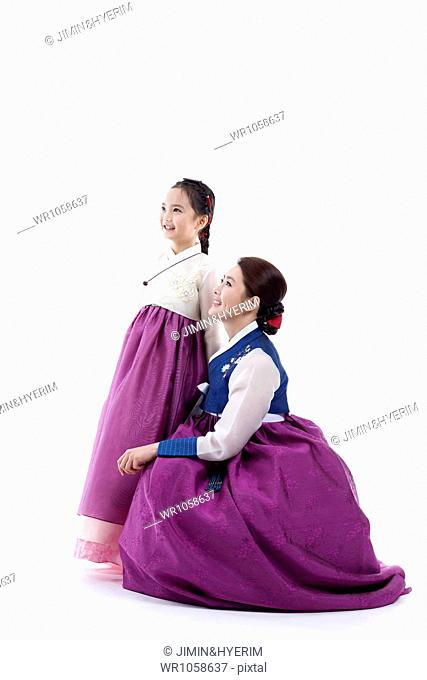 990c4f71a mother sitting down next to a daughter in Korean traditional costume