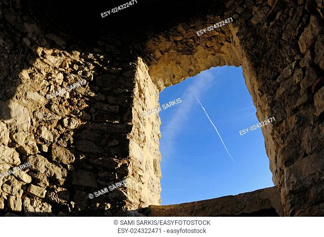 Old stone wall with window framing blue sky, Allauch, France
