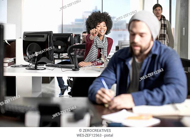 Smiling woman at desk in office pointing at colleague