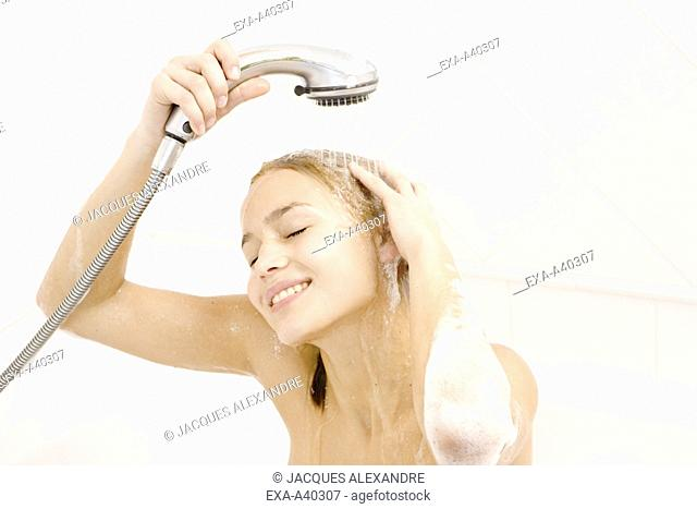 Young woman washes Shampoo out
