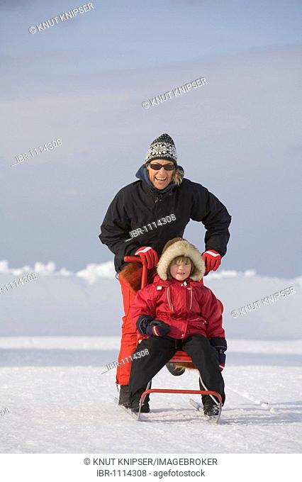 Woman and 4-year-old girl on a sledge in front of the ice hotel of Jukkasjaervi, Lappland, Northern Sweden