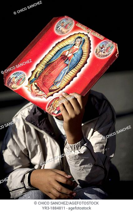 A pilgrim carrying an image of the Our Lady of Guadalupe covers his face from the sun outside of the Our Lady of Guadalupe Basilica in Mexico City, December 9