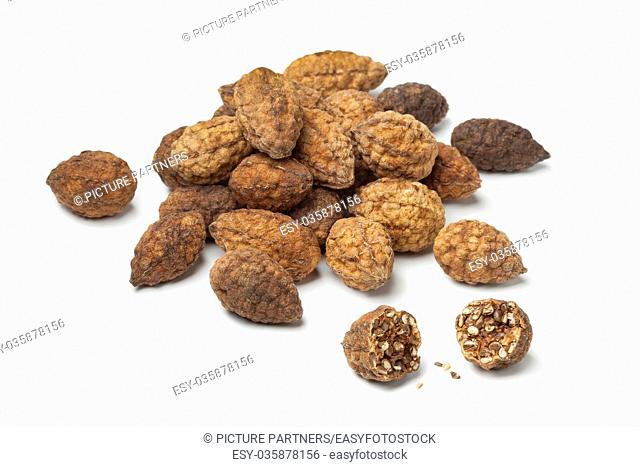 Heap of dried caperberries on white background