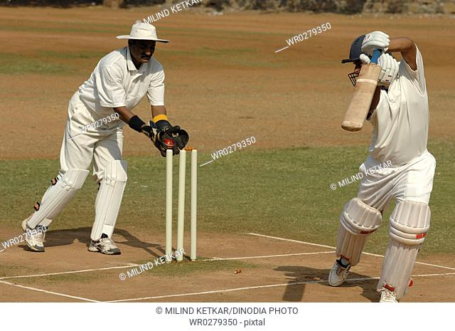 Batsman out of crease being stumped by wicketkeeper on pitch in cricket match MR705-J,705L
