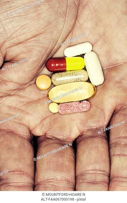 Assorted pills in man's hand