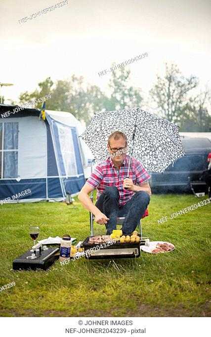 Man barbecuing in rain