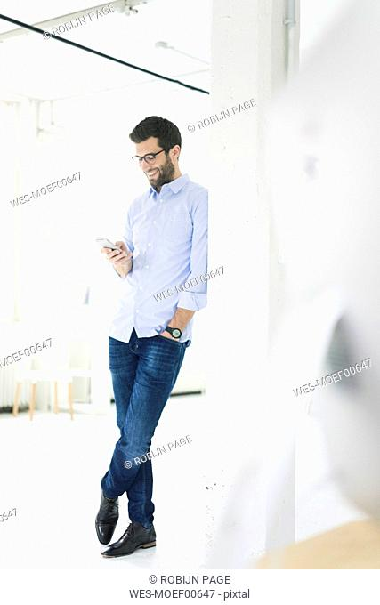 Smiling businessman looking at cell phone in office