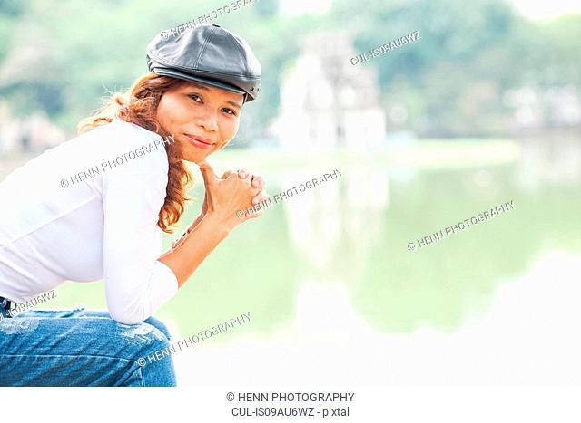 Portrait of woman wearing cap at Hoan Kiem Lake, Hanoi, Vietnam