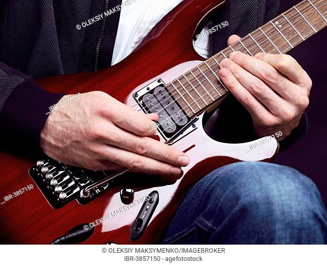 Closeup of man's hands playing red electric Ibanez guitar