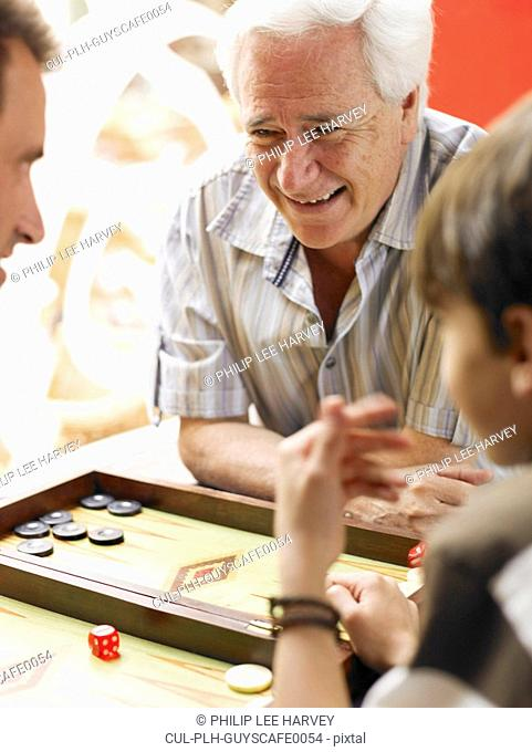 Boy 8-10 playing backgammon with father and grandfather differential focus