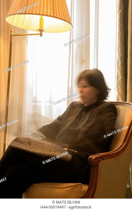 Woman Sitting in an Armchair and Reading a Newspaper and Illuminated From a Floor Lamp in Motion Blur in Cannes In Provence-Alpes-Côte d'Azur, France