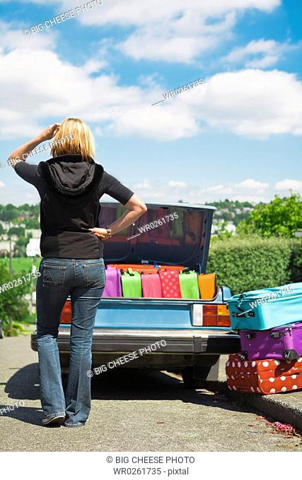 Confused woman loading car trunk with colorful suitcases