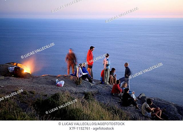 Pilgrims in Cape Finisterre  At left the pilgrims burn the clothes used during the peregrination to Santiago de Compostela  Finisterre Coruña province Spain...