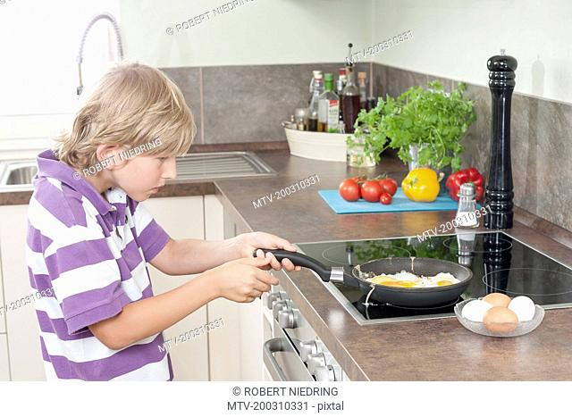 Boy preparing fried eggs in kitchen, Bavaria, Germany