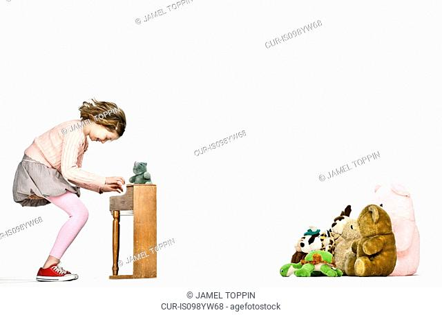 Girl playing miniature piano for teddy bears