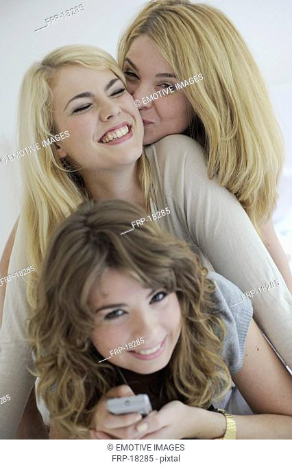 Three young women lying on top of each other