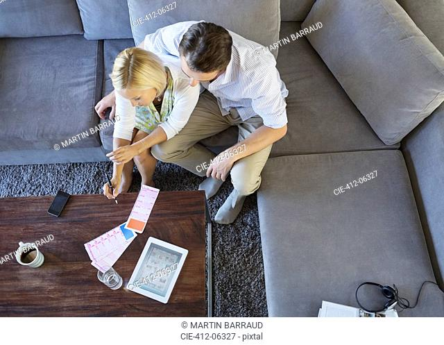 Couple using tablet computer on sofa