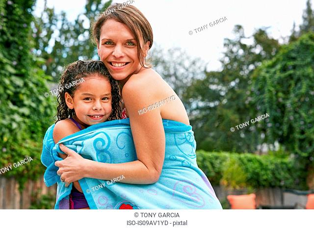 Mother and daughter wearing swimwear wrapped in towel looking at camera smiling