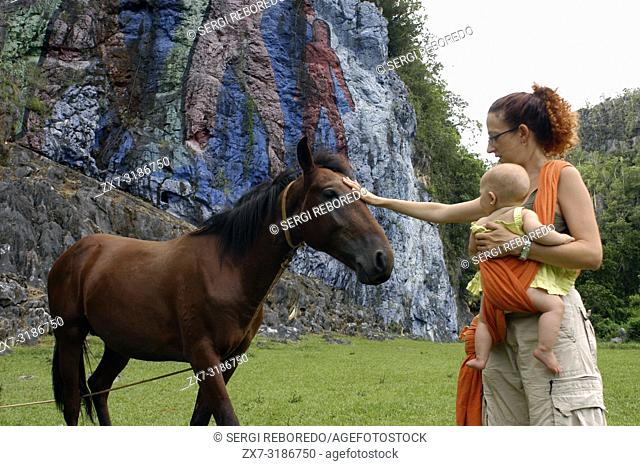 Mother with her baby and a horse in The Prehistory mural, Pinar del Rio, Cuba. Painted in the wall of a cliff is one of the popular attractions in the landmark