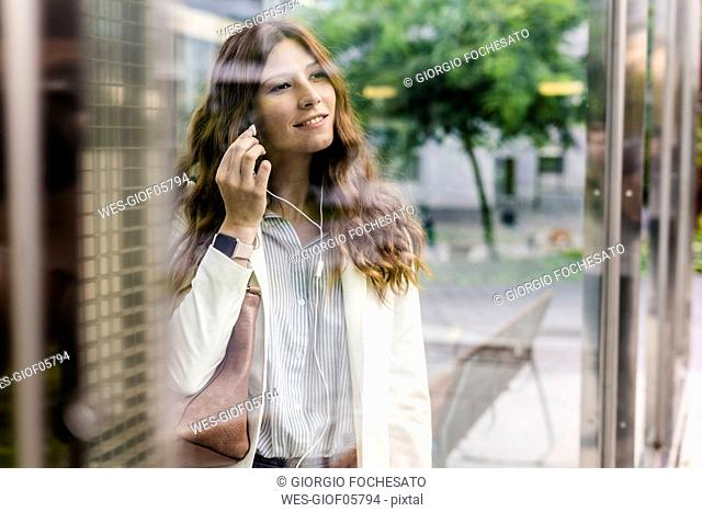 Young businesswoman communting in the city, using earphones