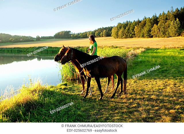 Woman with Two Horses in a Lake at Sunset