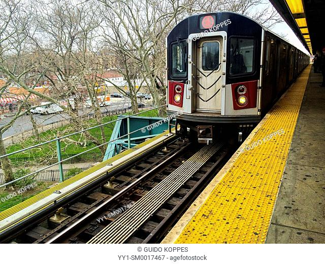 New york City, USA. Subway train arriving at an elevated subway train station in Brooklyn