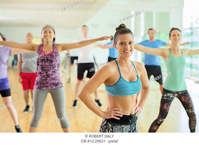 Portrait smiling fitness instructor leading aerobics class