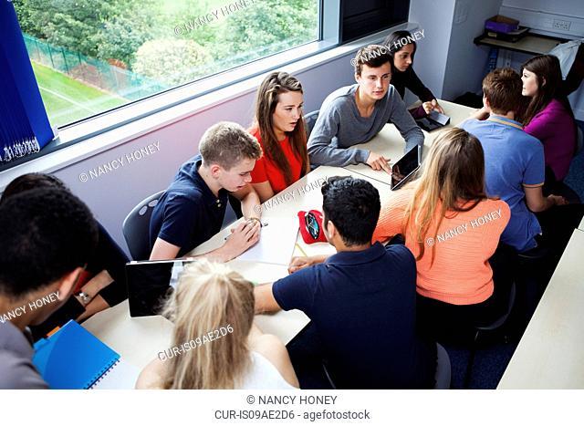 Teenage schoolchildren working together with digital tablet