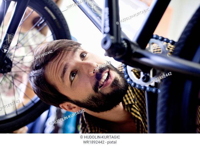 Man in bicycle shop looking at bike