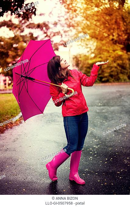 Happy woman with umbrella checking for rain in a park Debica, Poland