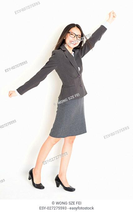 Portrait of happy Asian businesswoman in formalwear arm raised grabbing something and smiling, full body standing on plain background