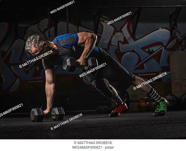 Mature crossfit athlete exercising with dumbbells in pushup position