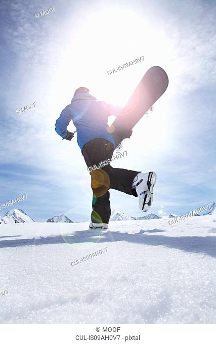 Mature man carrying his snowboard uphill, Obergurgl, Austria