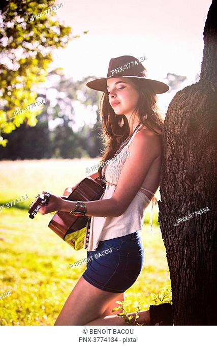Young woman back to a tree plays guitar