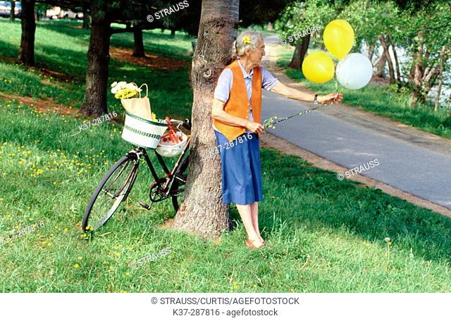 Senior woman with bike and balloons in park