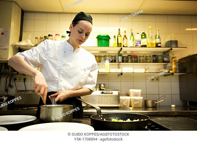 The chef of a vegetarian restaurant, preparing meals in the kitchen of the restaurant