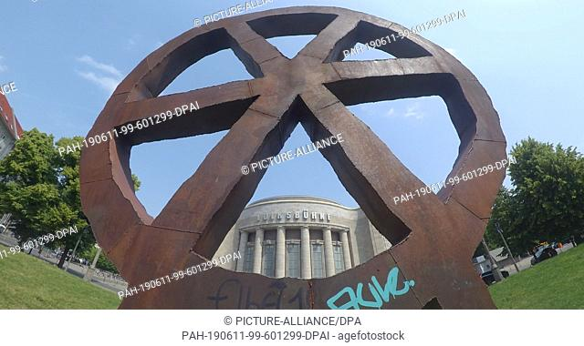 "11 June 2019, Berlin: The metal sculpture """"Räuberrad"""" in front of the Volksbühne. Berlin's Senator of Culture K. Lederer (left) wants to inform about the..."