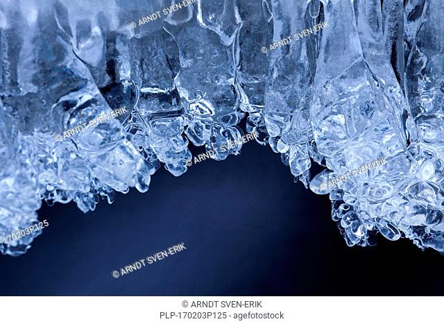 Ice formations and icicles formed by frost and freezing cold temperatures over running water of stream