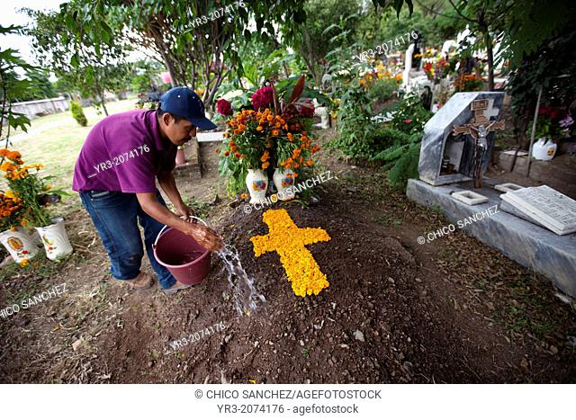A man waters a tomb decorated with a cross of marigold flower petals during the Day of the Dead celebrations in Teotitlan del Valle, Oaxaca, Mexico