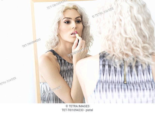 Studio shot of young woman applying lipstick