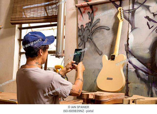 Guitar maker in workshop photographing guitar