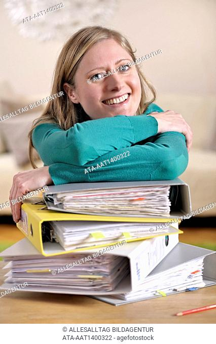 Woman in front of a big pile of files