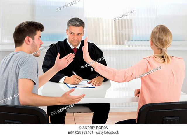 Young Couple Having An Argument In Front Of Male Judge At Desk
