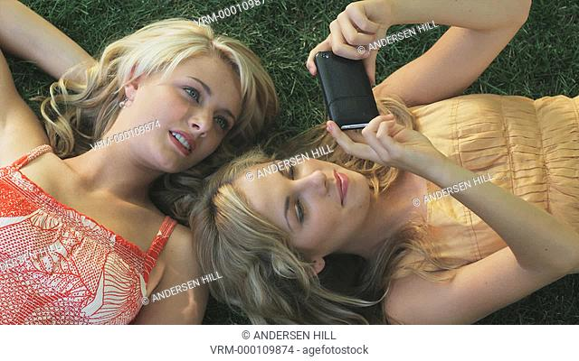 two women lying on the grass looking at a cell phone
