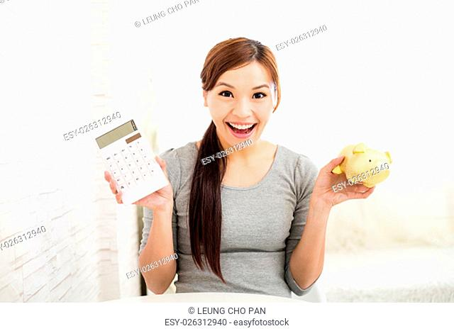 Woman holding a calculator and piggy bank