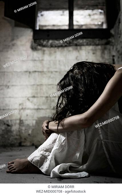 Despaired woman sitting in cellar