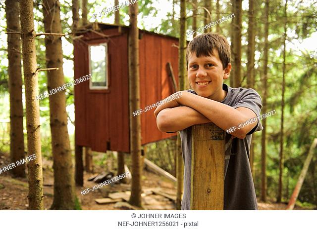 Teenage boy leaning on wooden plank in front of cottage