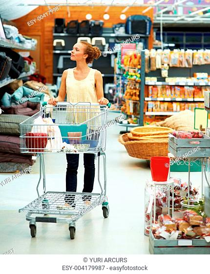 Attractive young woman walking and pushing trolley in large store looking around
