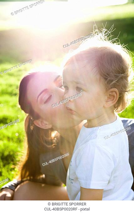 Mother kissing toddler in park